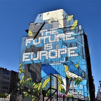 Kuvituskuva, jossa rakennus, jossa iso muraali, jossa lukee The future is Europe. Tekstin alla on sininen lintu.